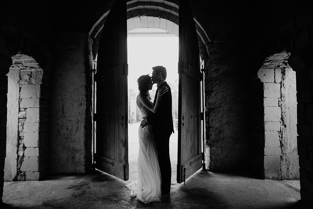 backlit portriat of bride and groom in a wooden doorway