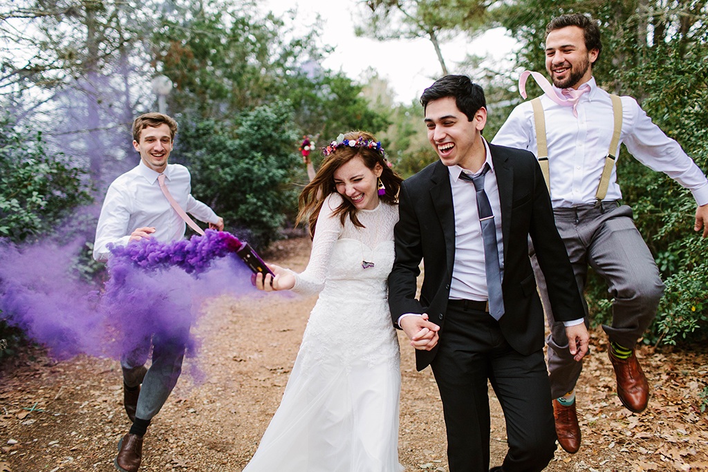 bride and groom with bridal party and purple smoke bomb
