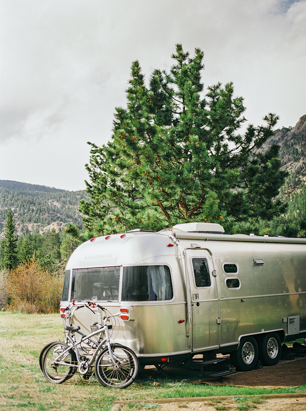 an airstream with bikes parked in the camp grounds of the Rocky Mountain State Park