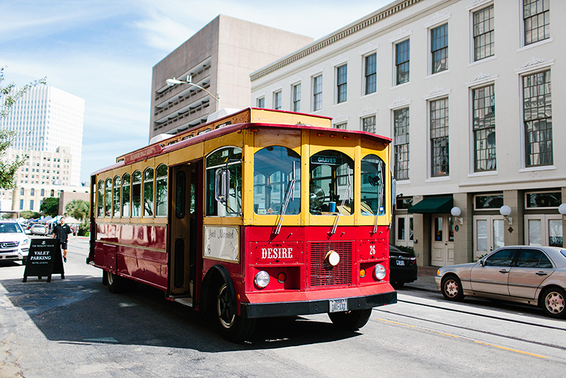 red trolley infront of the Tremont House Hotel in Galveston Texas