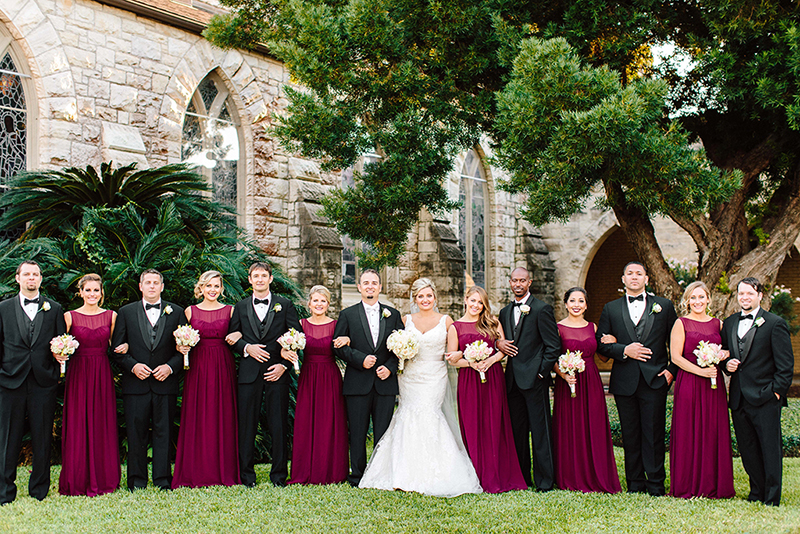 Beautiful wedding party wearing Fall colors infront the Grace Episcopal Church marsala bridesmaids dresses
