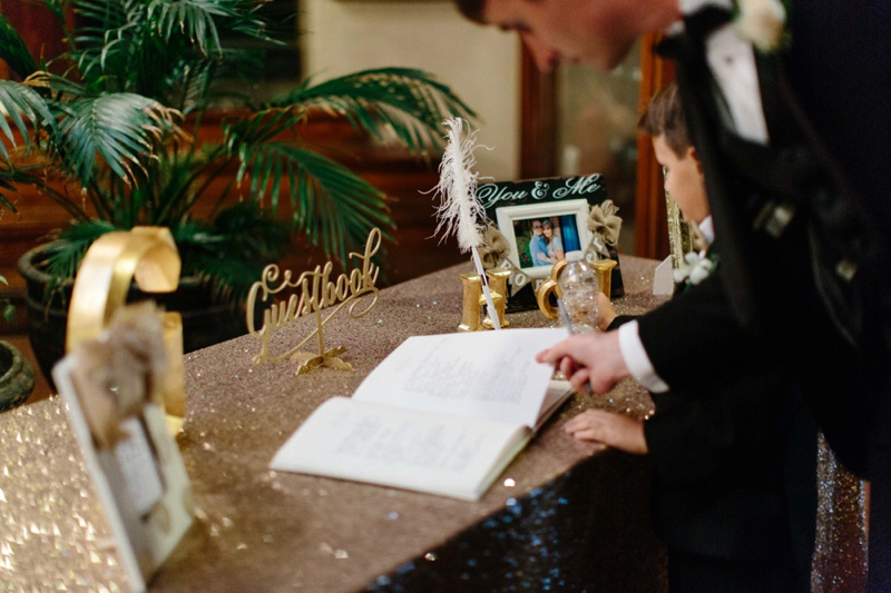 People signing a wedding guest book at a reception