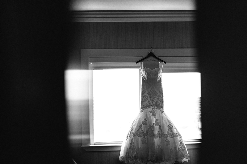 black and white photo of a wedding dress hanging in a hotel room