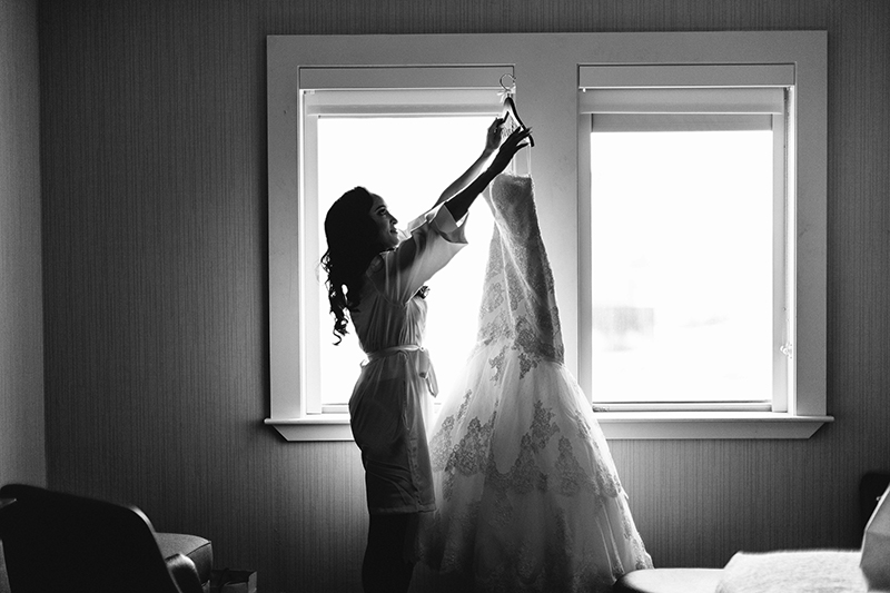 black and white photo of a bride holding up her wedding dress in a hotel room